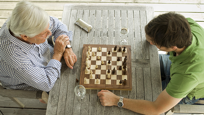 father son playing a game of chess